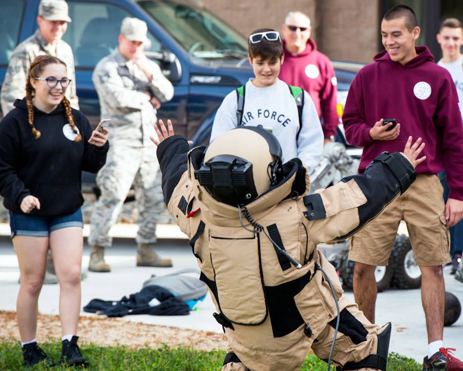A student from Whitney High School, Rocklin, Calif., falls backwards from the weight of the Explosive Ordnance Disposal 9 suit during Travis Tour Day. Students toured several aircraft, air traffic control tower, dormitories and had the opportunity to talk with Travis Air Force Base personnel about military life. The purpose of the tour is to support Air Force recruiting by inspiring patriotism and encouraging young men and woman to serve in the military.