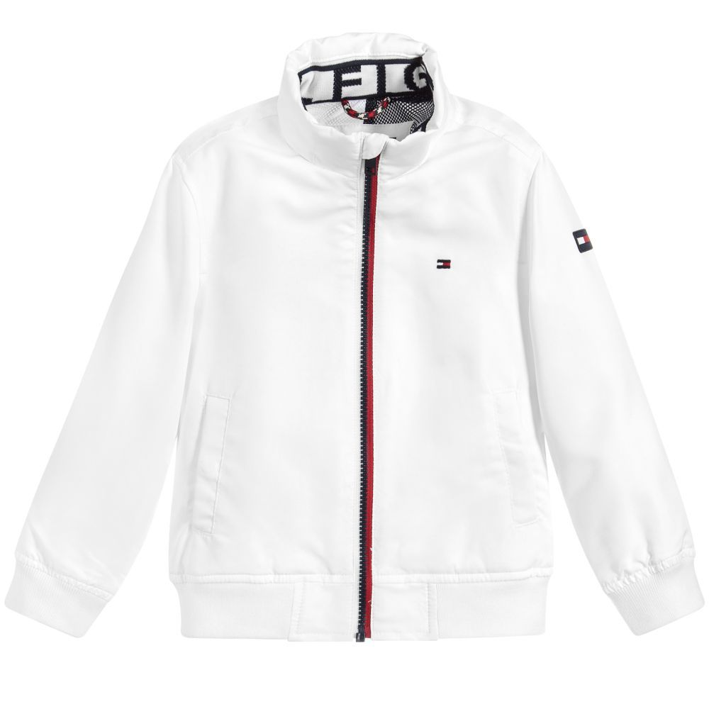 681cd1b0a069 Boys white bomber jacket from Tommy Hilfiger. It is lightweight with soft  mesh lining and has a concealed hood in the collar. It has a red stripe down  the ...