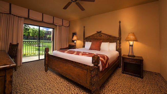 Bed, wood headboard carving with The Lion King designs, end table, chairs, patio view, lamps and fan