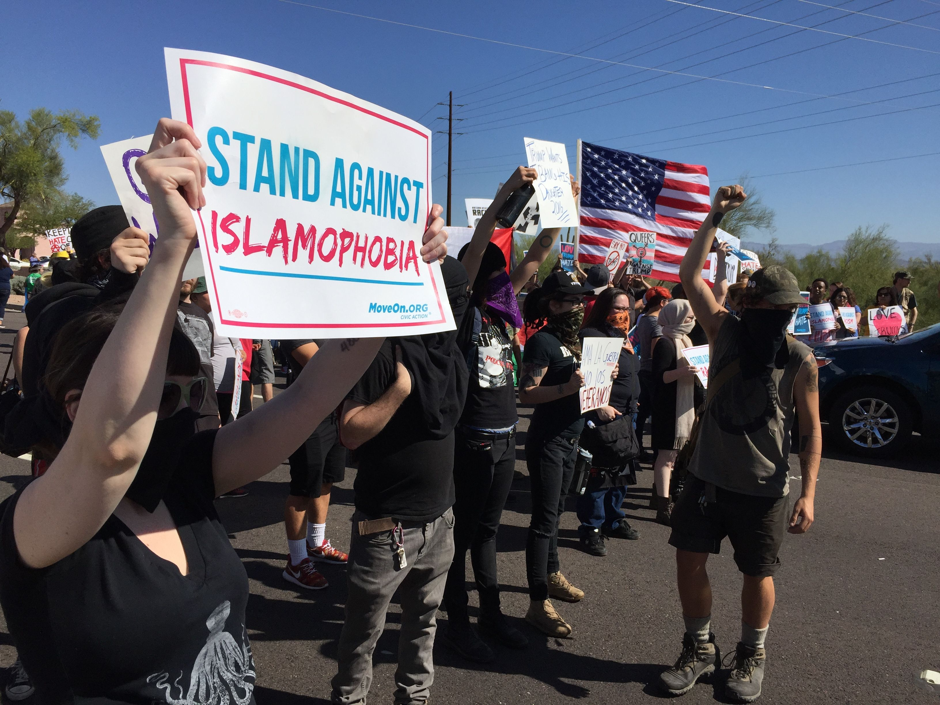 "A woman holds a sign reading, ""Stand Against Islamophobia"" during a protest outside a Donald Trump rally on Saturday in Fountain Hills, Arizona. Photo by Simon Moya-Smith, ictmn.com."