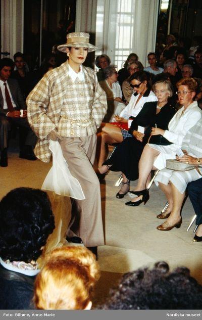 Modevisning. Modell i rutig jacka och hatt, vida byxor i beige ton och vit scarf i handen. Från Chanel.