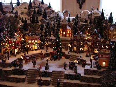 the sugary rock mountain and candy coated village at the yacht club resort is circled by a model train - Christmas Town Decorations