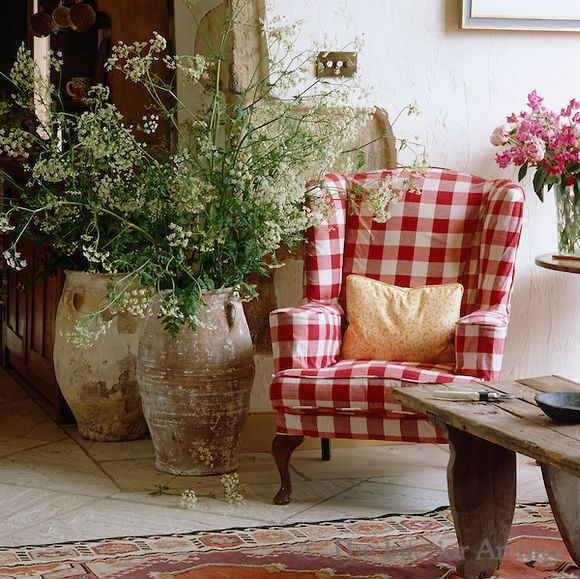 A wing-backed armchair in the living room, upholstered in red and white gingham, is placed next to two large earthenware urns filled with cow parsley -- Credit: Fritz von der Schulenburg/The Interior Archive -- Designer/Stylist: Emily Todhunter
