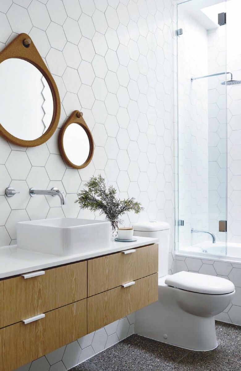 White hexagon tiles on the wall, round mirror with wooden frame ...