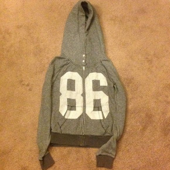 Victoria's Secret PINK hoodie Light grey PINK hoodie. Size medium. The hood is slightly oversized and very unique with button closure.  LOVE PINK is on the back in sewn on fabric and 86 on the front in white screen print. Lightly worn and free of stains and blemishes.  No trades. Victoria's Secret Tops Sweatshirts & Hoodies