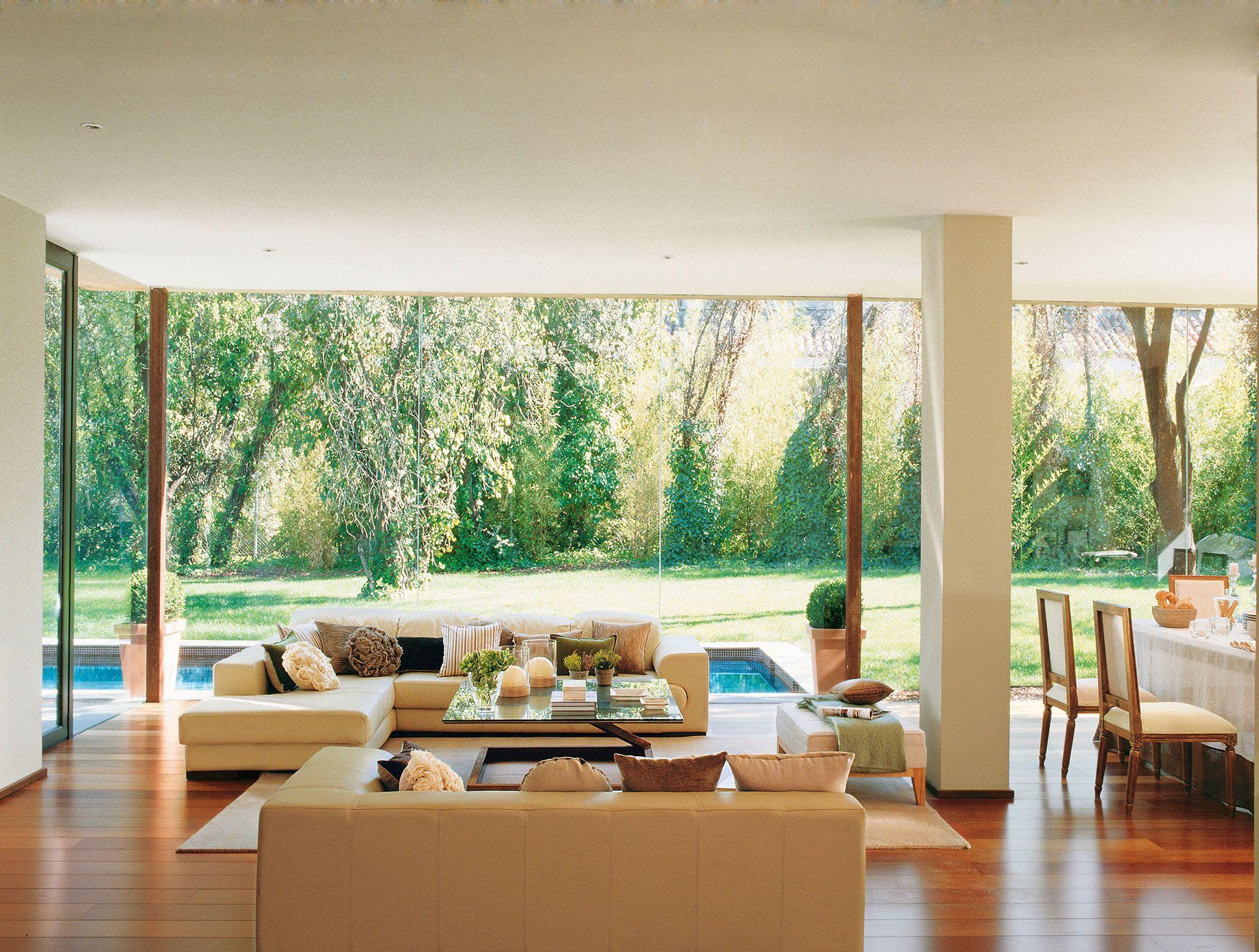Salón con diseño de lineas rectas y pared de cristal hacia la ...