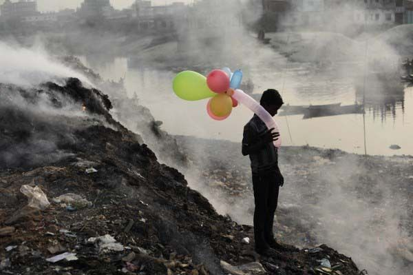 Image result for COLORFUL BALLOONS A boy plays with balloons by Buriganga river as smoke emits from a dump yard during sunset in Dhaka, Bangladesh.