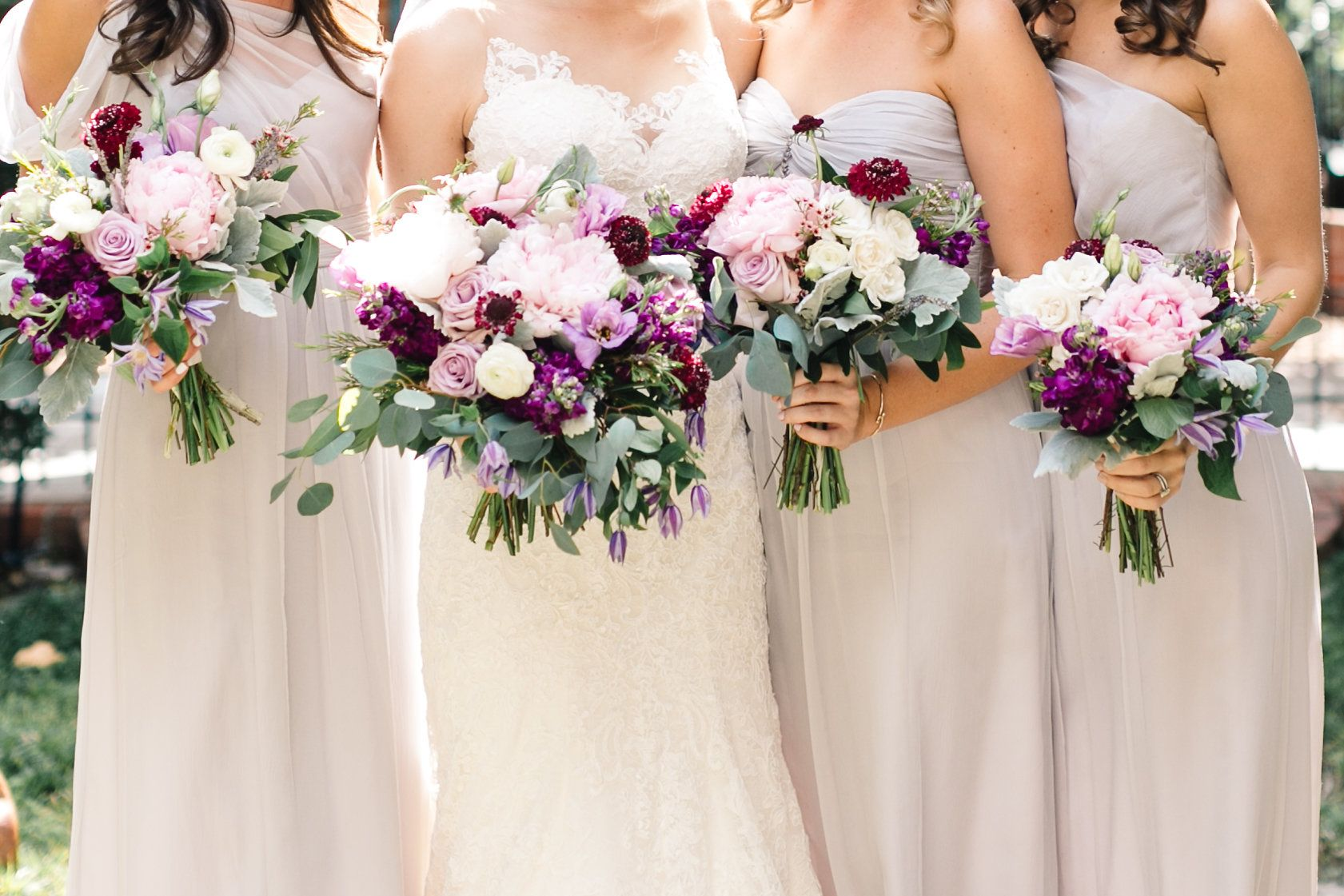 Bride And Her Bridesmaids In Pale Grey Gowns Carry Their Bouquets