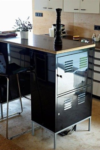 Close up of glossy black filing cabinet used an island in the middle of a kitchen.