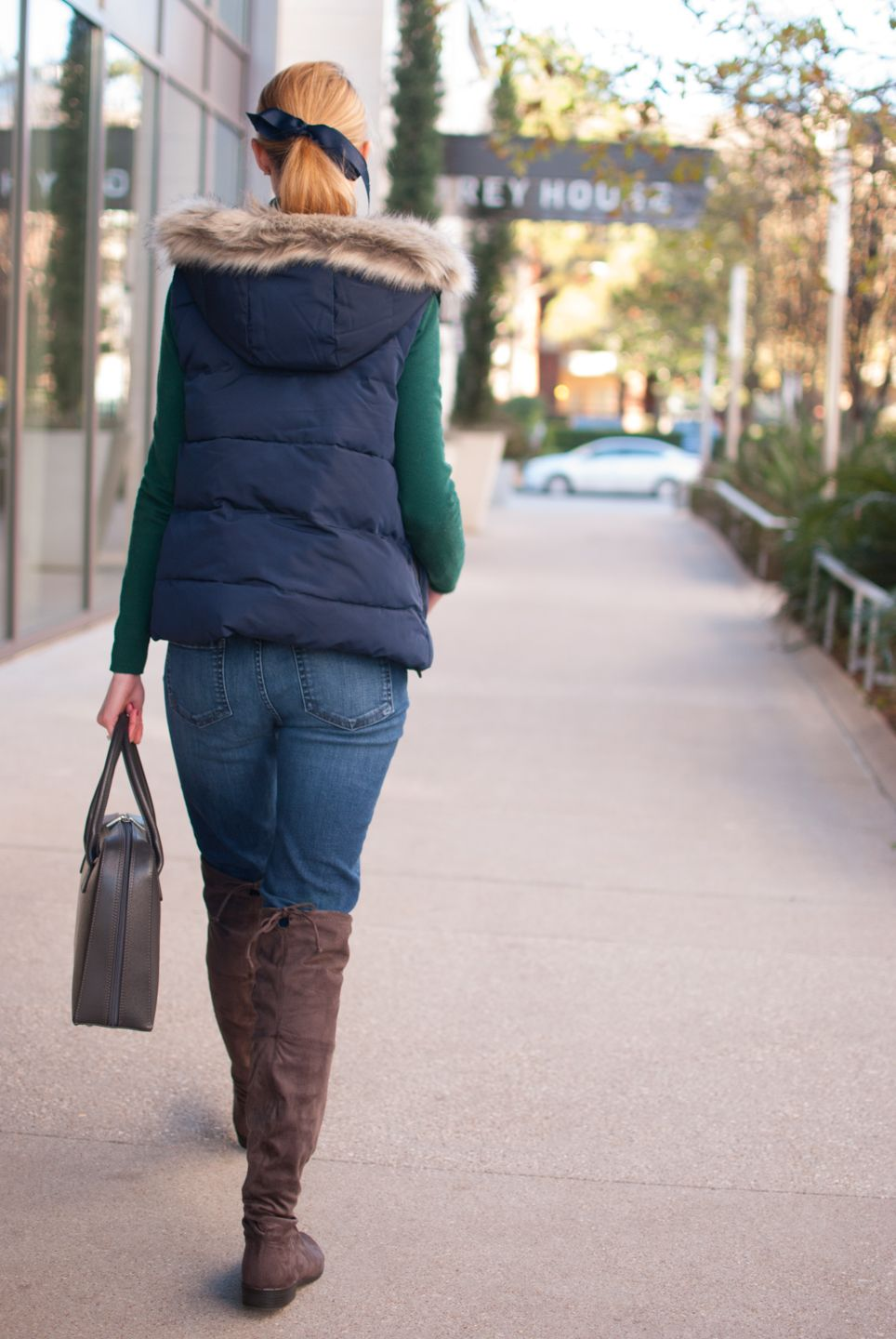 Casual winter look with a navy puffer vest and gray suede over the knee boots
