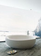 White round bathtub against window with snowy landscape view