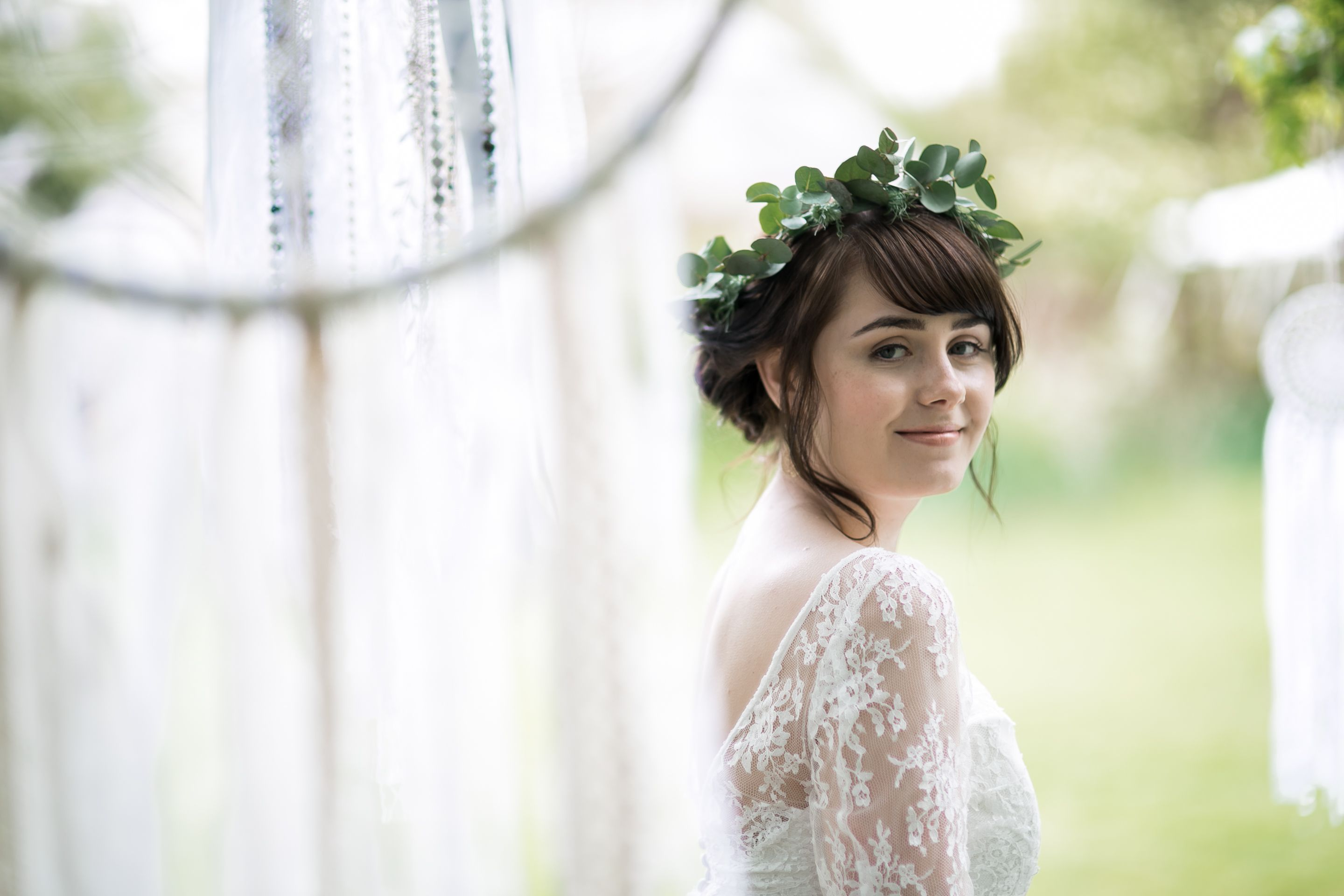 Boho bride with floral crown amongst handmade dreamcatchers from a