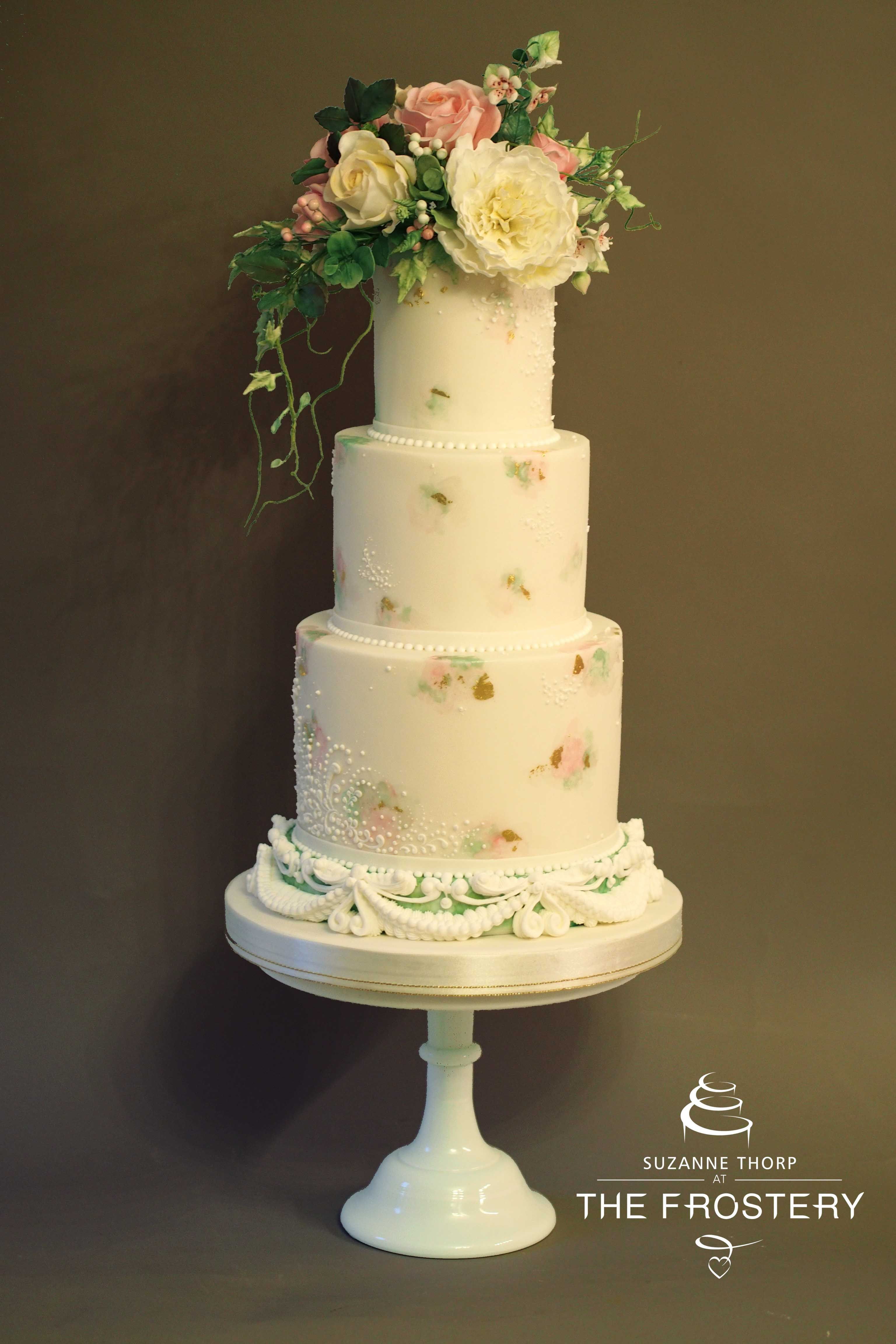 Romantic 3 tier wedding cake with oversized bouquet, over piped base ...