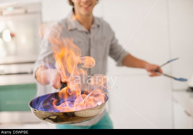 Man cooking with fire in kitchen. © Bill Cheyrou / Alamy