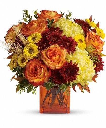 The stylish contemporary arrangement includes yellow cushion spray chrysanthemums, bi-color orange roses, rust cushion spray chrysanthemums, yellow disbud chrysanthemum and yellow Viking spray chrysanthemums. #FallFlowers