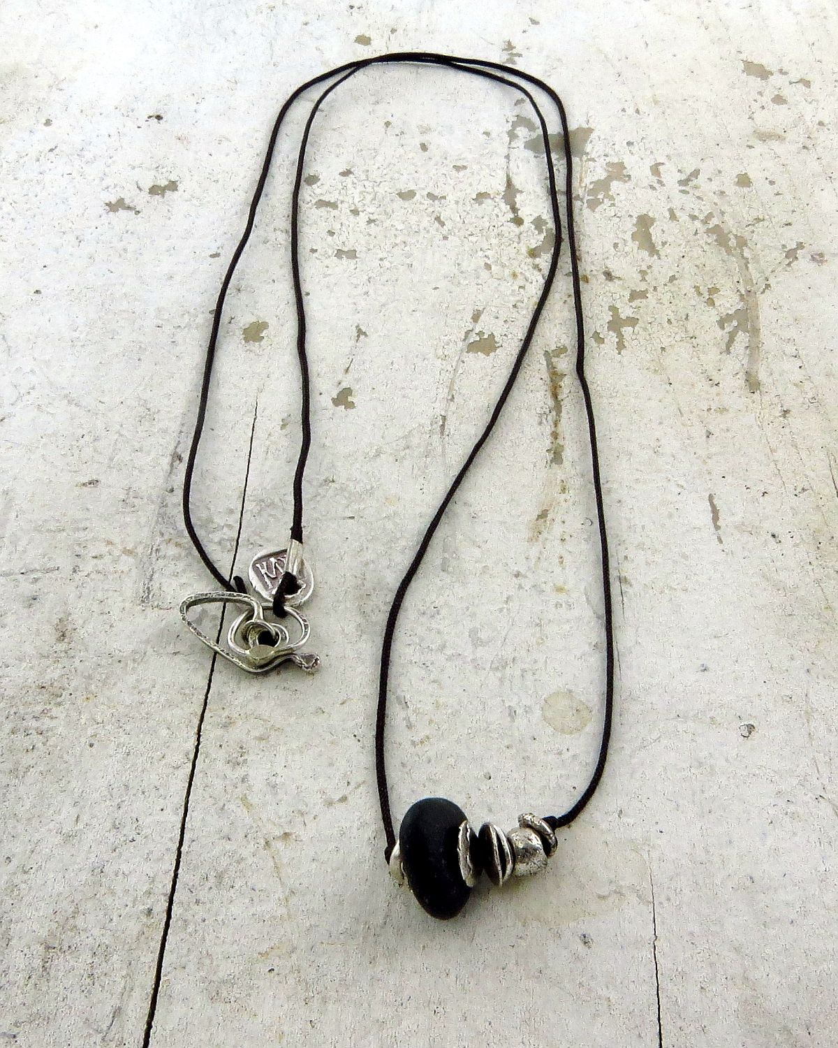 A very minimal yet organic necklace ... fine silver discs and nuggets surround a tiny black beach pebble ...