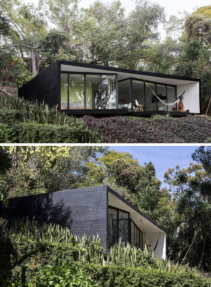 This small house has been covered in black siding to give it a modern feel and conceal it in the dark forest around it