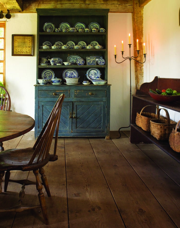 The fine old blue paint of a cupboard in the dining room resonates with the Canton china on its shelves. A beautifully formed Pennsylvania bucket bench, in original paint, holds some of the couple's prized baskets.
