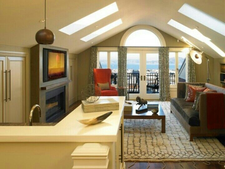Attic Living Room With Fireplace And Skylights Above Garage