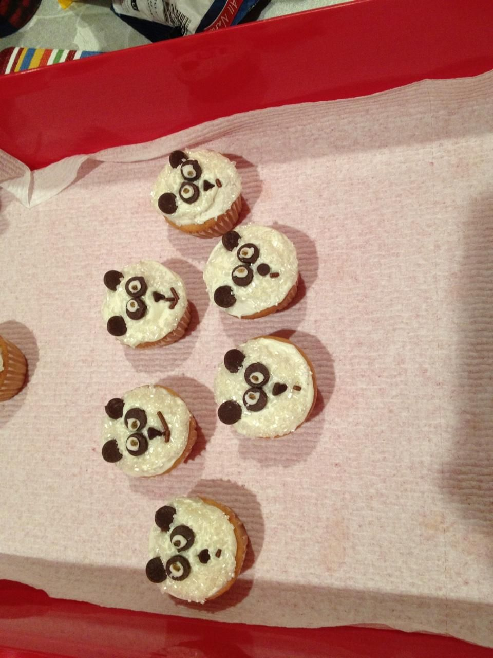 Mini panda bear cupcakes made with mini chocolate chips for nose, reg chocolate chips for the eyes and ears and sprinkles for mouth and white of eyes...I used edible ink on eye sprinkles.