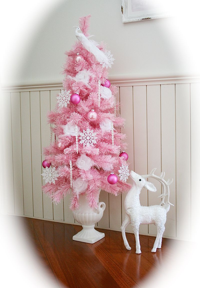 this pink tree is affixed in a white vase and is looking stunning the decoration is done with snowflakes ornaments and tulle - Pink Christmas Trees
