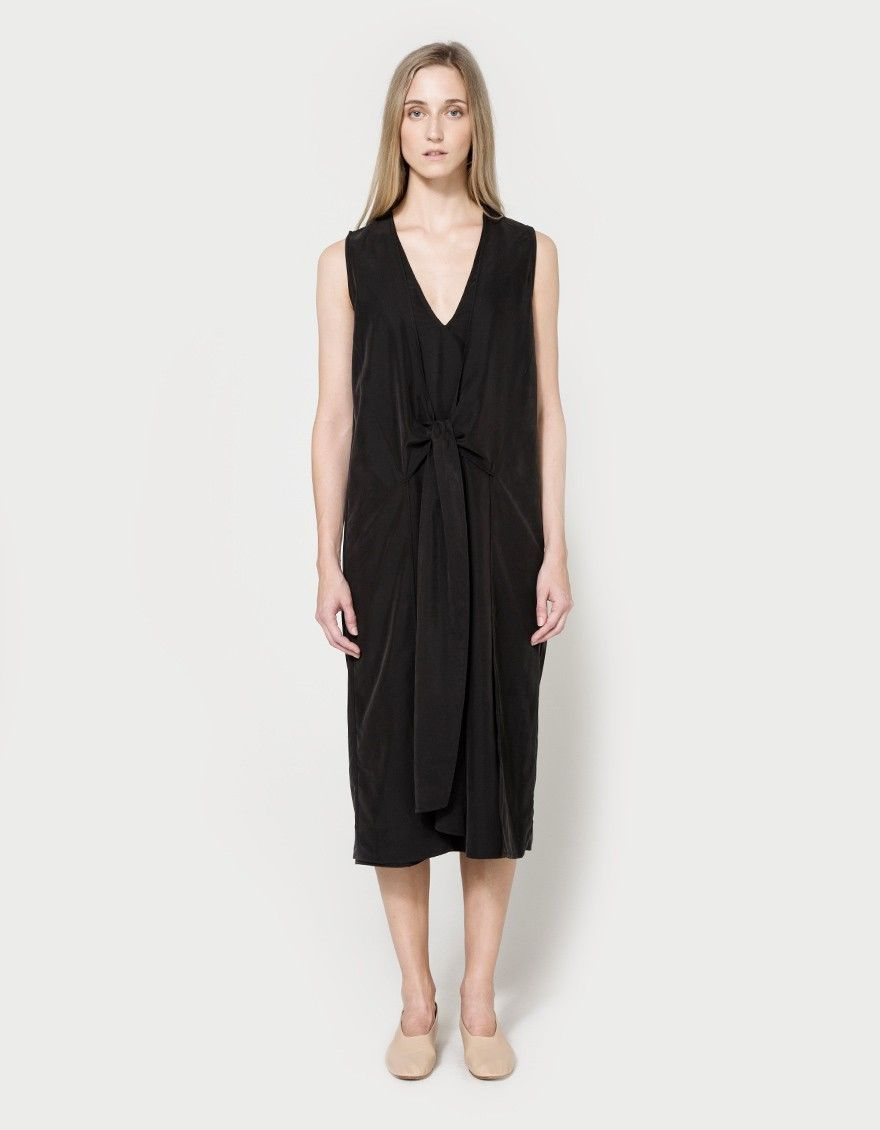 Sleeveless shift dress from NEED in a washed Black. V-neckline. Wrap-over panels with center-front tie closure. Straight back yoke with box pleat details. Dual vents at front hem. Unlined. Made in USA with imported materials.  • Rayon blend • 70% modal