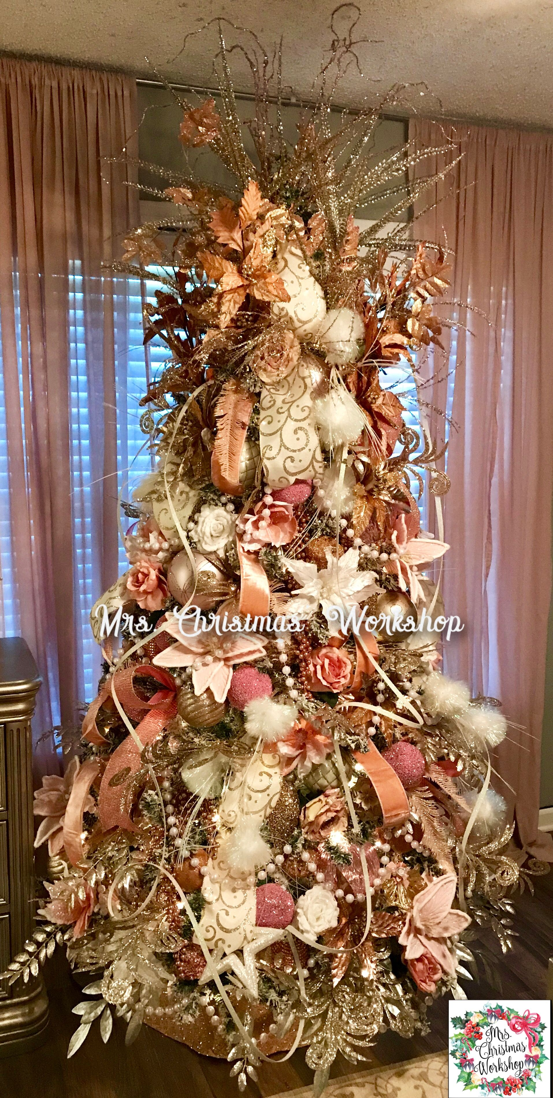Gold and pinks on the Christmas tree with large pearl garland and feathers  and flowers. Very wide ribbon as well as think spiral ribbons running down  tree.