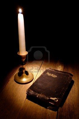 Old and damaged Holy Bible antique religious book with torn cover lit by the soft and warm glow of a candle light on a vintage candlestick on an aged wood table  Stock Photo - 13360097