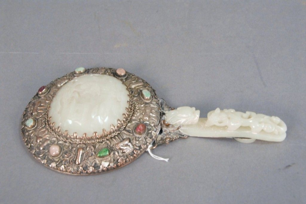 Carved white jade and silvered hand mirror comprising of white jade carved foo dog belt hook handle and an oval white jade plaque -  Realized Price: $4,537.50