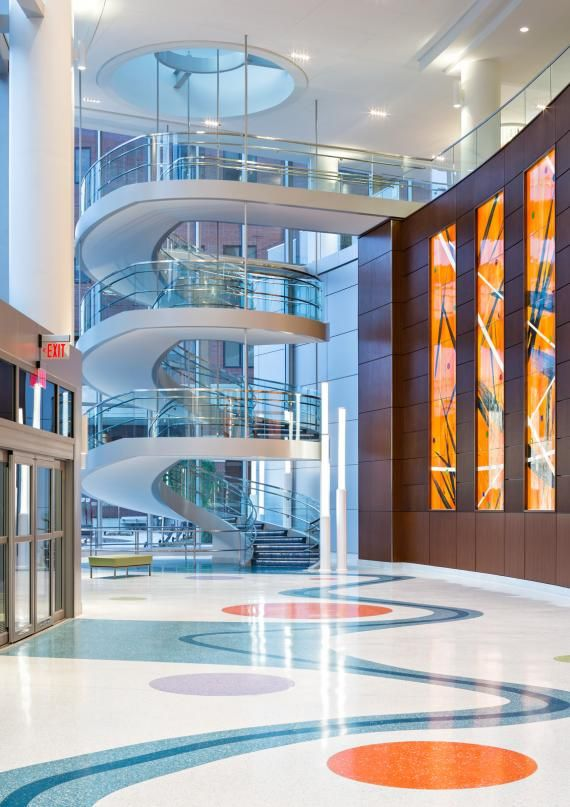 Lobby view the dramatic spiral stair and glass elevators for Entice architecture interior designs