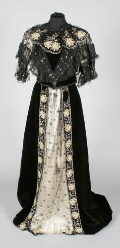 An Edwardian black evening dress comprising a bodice and skirt, with net trim and yellow braiding with silver sequin beading, the cream fine silk voluminous gown has free-flowing lace panels, trimmed with peach bows. Via Bonhams.