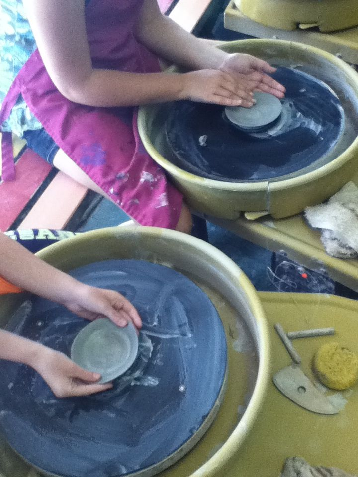 Children throwing bowls on the pottery wheel during art camp.