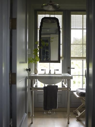 Open Washstand With Marble Top In Front Of Low Window With Mirror