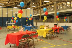 Tables with centerpieces and balloons in the theme's color. The centerpieces were popcorn bucket raffle prizes for the guests.