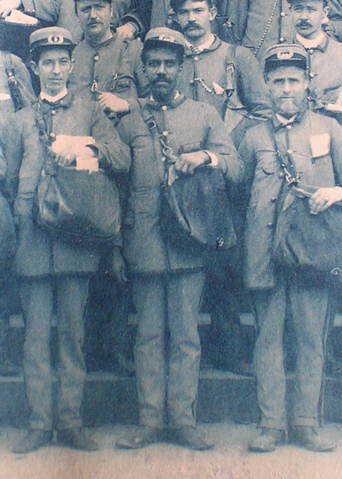 Uniformed letter carriers pose with their satchels in