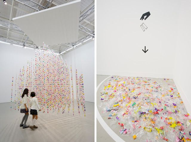 """An interactive installation at Shiseido Egg Gallery titled """"eat me."""" Roughly 7000 individually packaged candy was hung from the ceiling in the shape of a house. Visitors were encouraged to eat the candy but dispose of the wrappers in the corner of the gallery. The house eventually disappeared at the hands of the visitors, leaving just a pile of trash."""