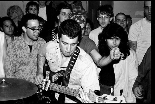 The Minutemen, house party, Hollywood, 1982. Mike Watt playing Earl Liberty's bass. The guy in glasses to the left of Watt is Spot, producer of all the early SST records by Black Flag, Hüsker Dü, the Minutemen, Meat Puppets, and others. (Jordan Schwartz)