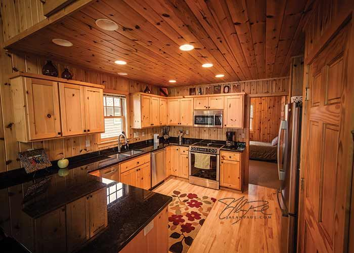 pine kitchen cabinets and black granite countertops complete the look of this lake home on big on c kitchen id=24608