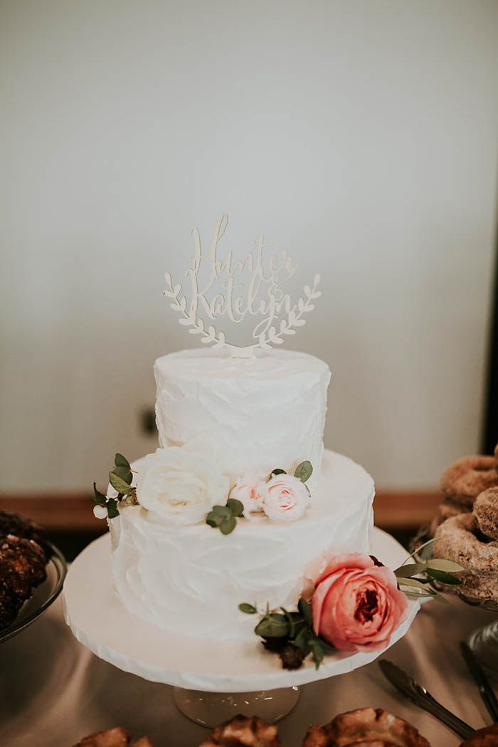 White 2-tier wedding cake with pink and white roses | Image by Olivia Strohm Photography