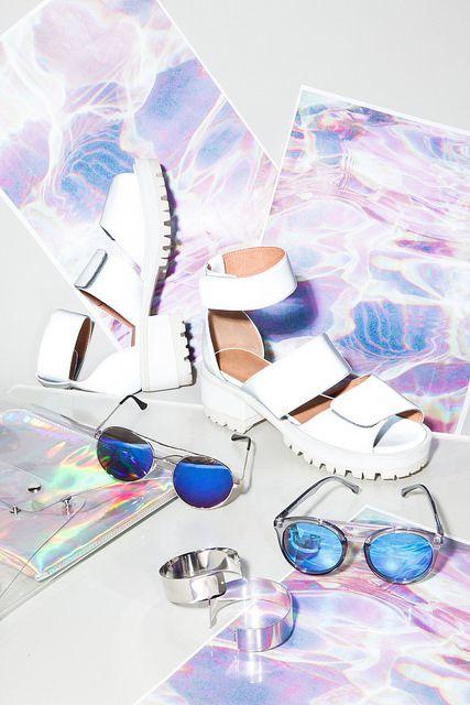 sapatos brancos, óculos azuis e braceletes metalicos com estampa holográfica