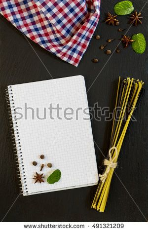 Blank cookbook with conventional and black uncooked Italian pasta Linguine, checkered napkin, spices and herbs on black stone background.