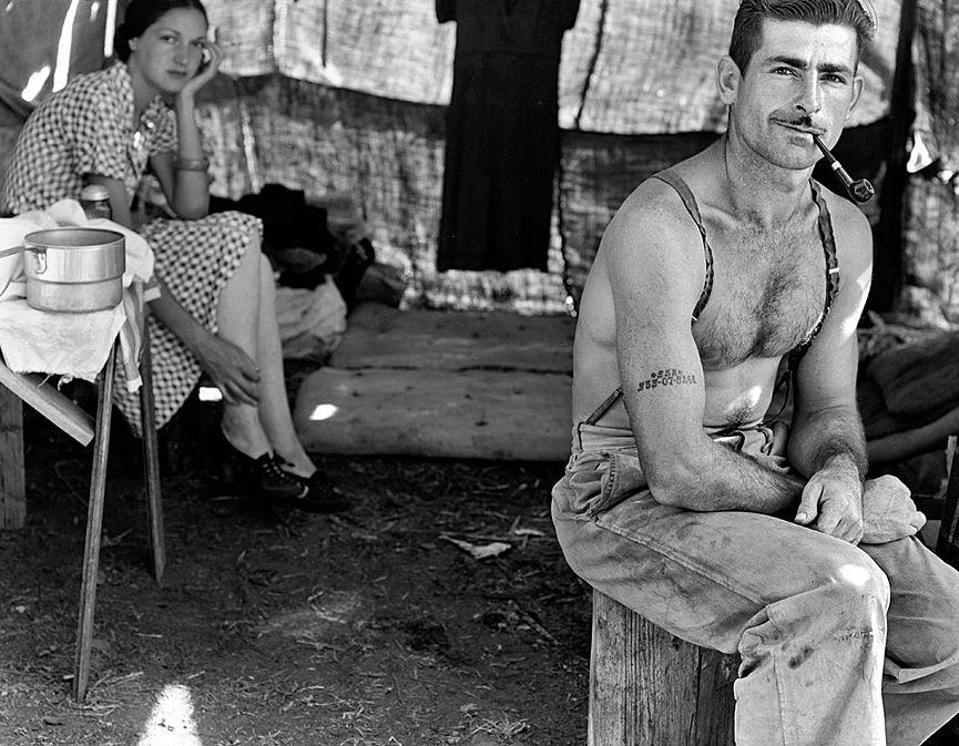 (Dorothea Lange)Thomas Cave, trabajador desempleado de la madera, con su esposa, cerca de West Stayton en Oregón, en busca de trabajo en la cosecha de frijoles. Es increíble ver que a pesar de la situación en la que se encuentran, van bien aseados y parecen felices. Thomas lleva tatuado en el brazo su número de la seguridad social.