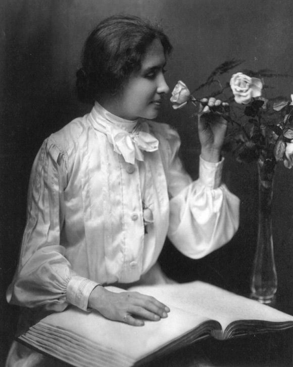 Helen Keller reading a Braille book and smelling a rose. In 1964 ...