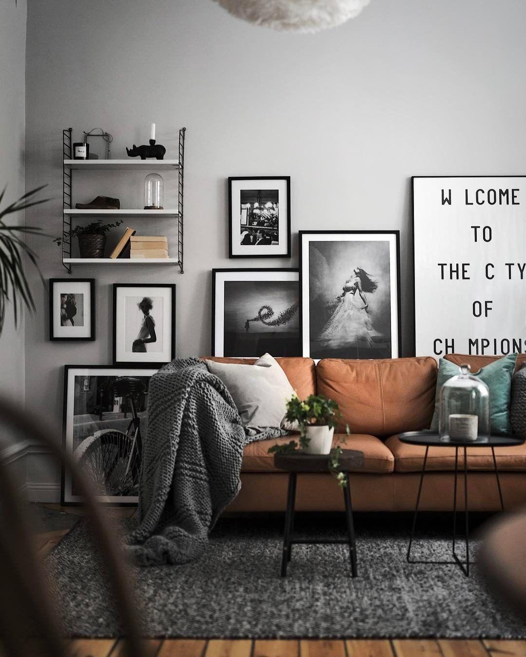 Gemütliches Wohnzimmer Mit Braunem Leder Sofa Und Modernen Deko Elementen.  Interessante Schwarz Weiß Bilder.