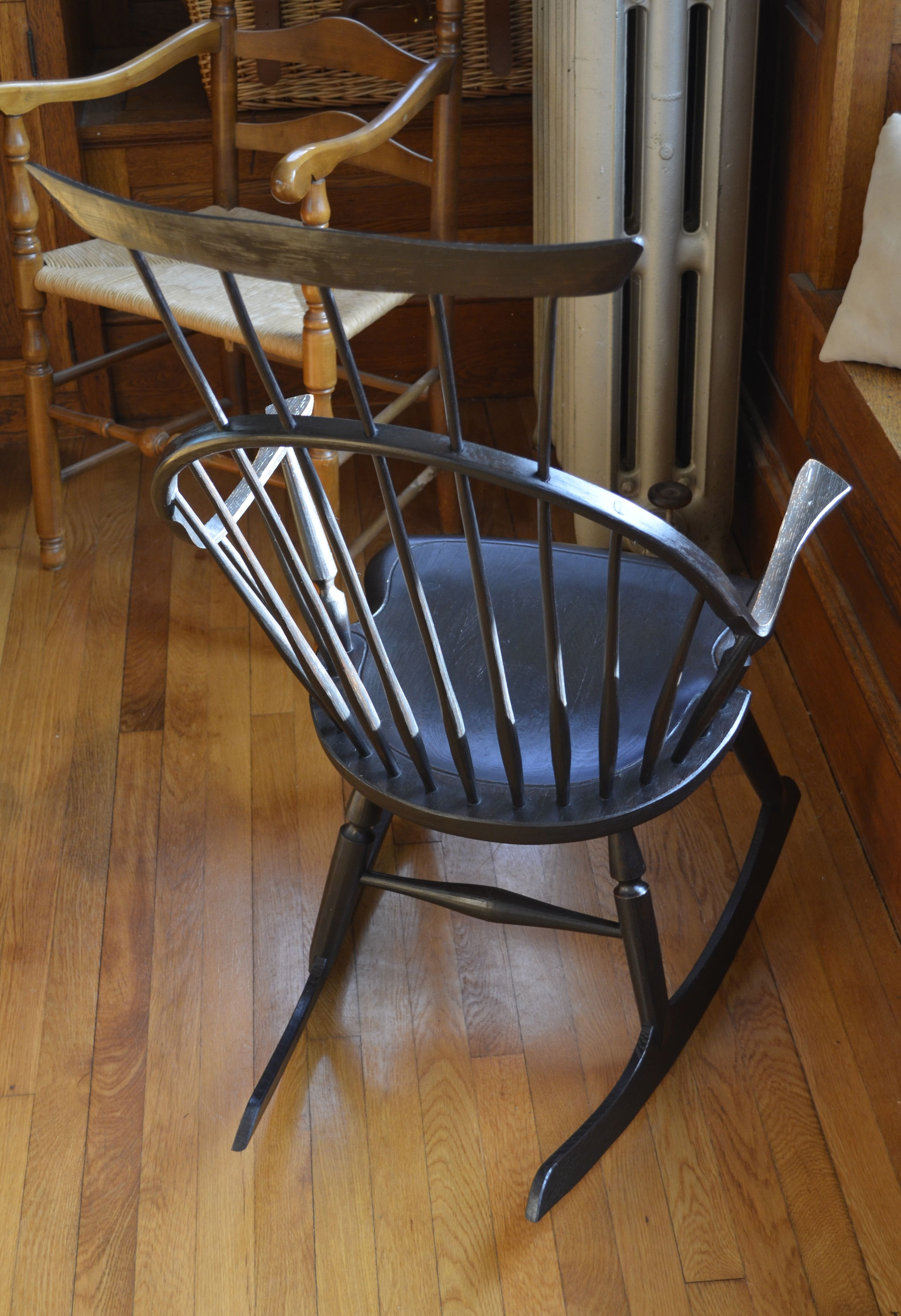 Continuous arm crested rocking chair with black over red