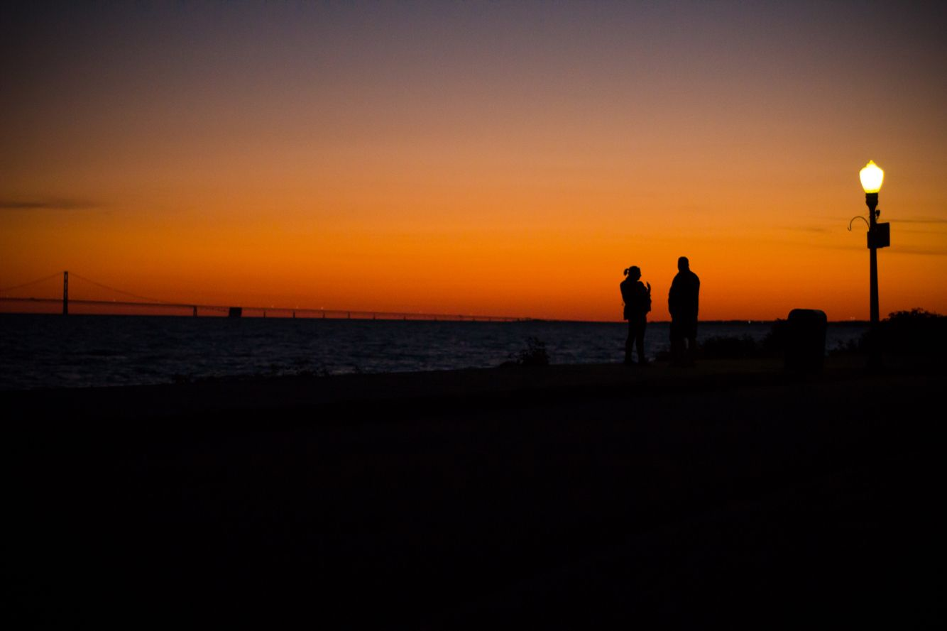 Couple on mackinaw island sunset. Mackinaw bridge in the background