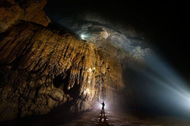 """Hang Son Doong, l'immense grotte vietnamienne La tâche la plus ardue de l'expédition consistait à ouvrir une voie pour passer au-dessus «la Grande Muraille du Viêt Nam» - une masse rocheuse en surplomb qui bloquait l'accès à une partie de Hang Son Doong. Les alpinistes aguerris """"Sweeny"""" Sewell et Howard Clarke cherchent ici des points d'ancrage pour supporter leur poids avant d'essayer d'escalader ..."""