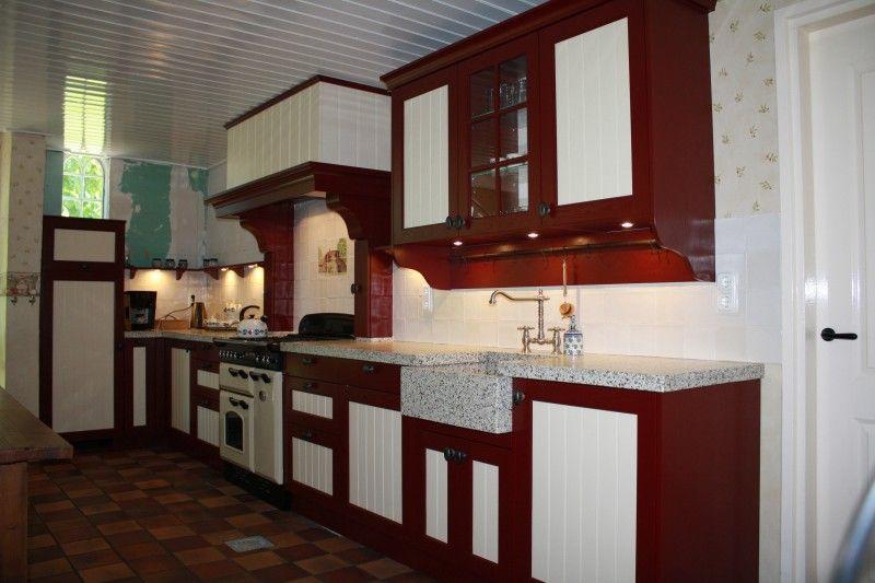 Rood/gele keuken met landelijk terrazzo blad en  schouw met kruidenkasten