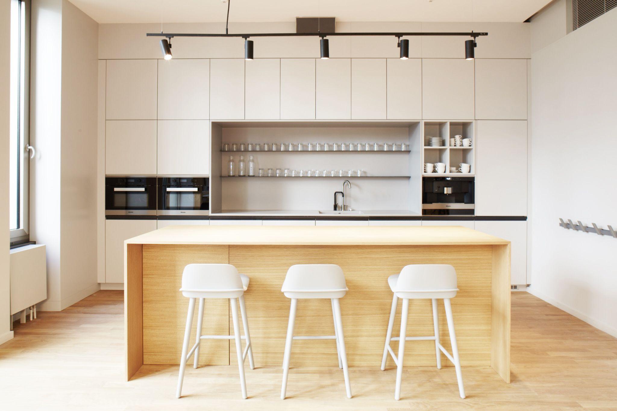 helle, freundliche Küche in hellgrau, kombiniert mit einem Hochtisch ...