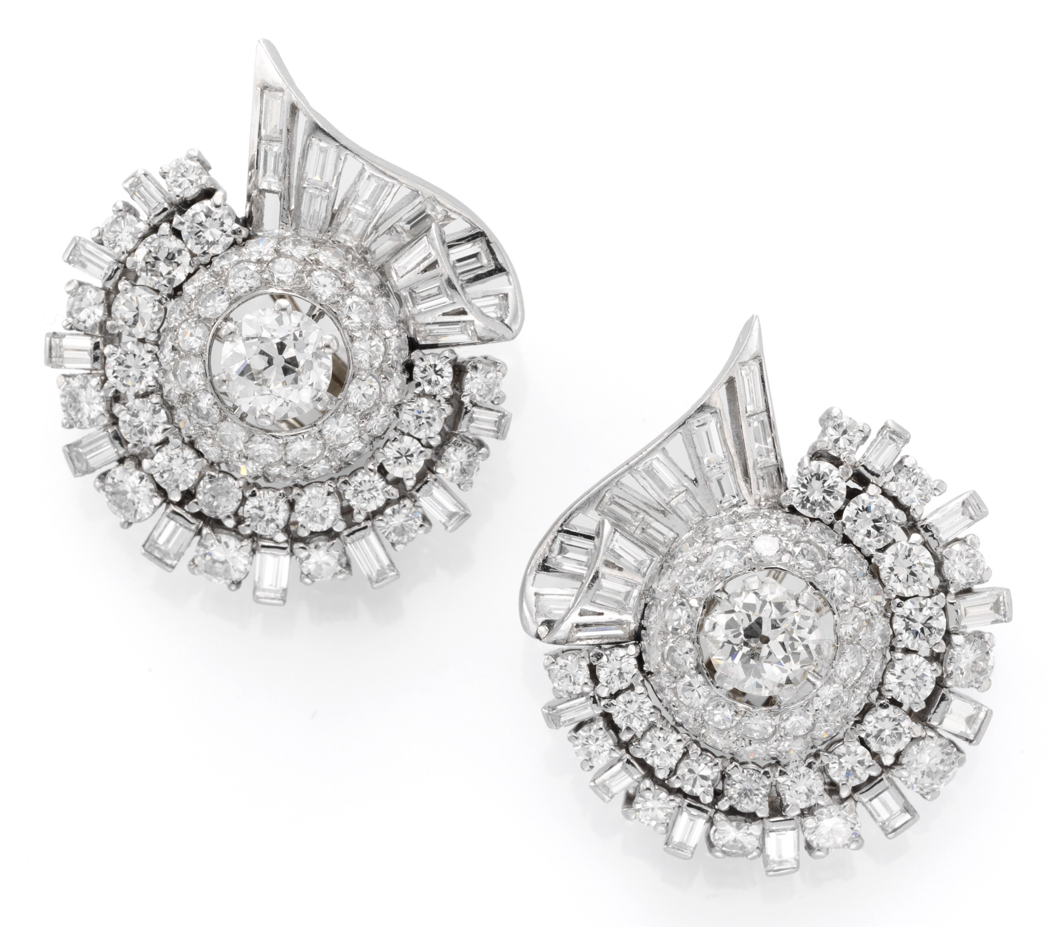 A pair of platinum and diamond ear clips of a scrolling design